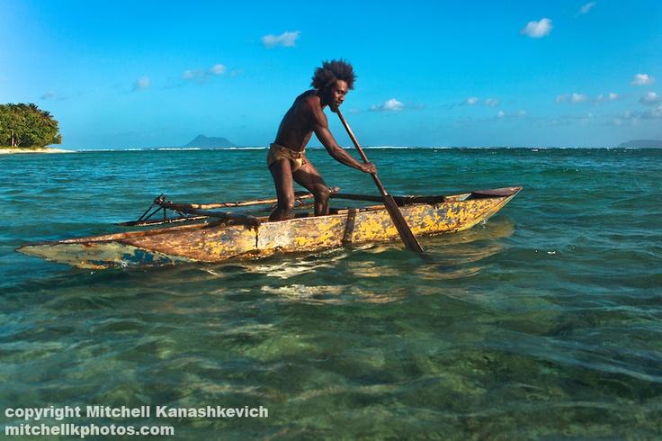 Ni Vanuatu man paddling a traditional outrigger canoe out to sea. Rah Lava Island, Torba Province, Vanuatu