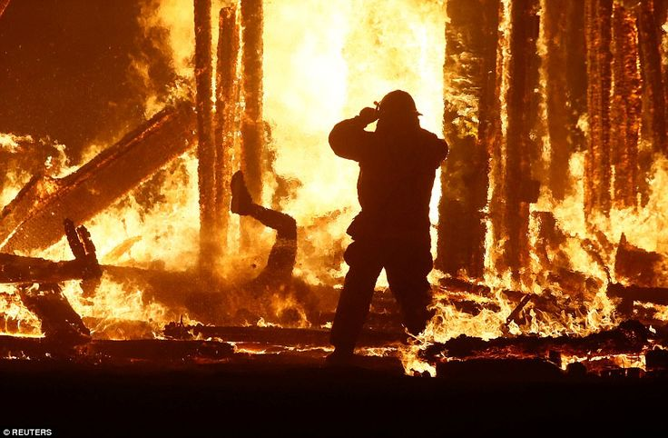 """A firefighter watches as a Burning Man participant (L) evades a chasing firefighter and falls into the flames of the """"Man Burn"""""""