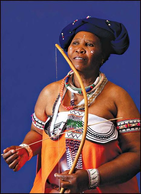 Xhosa woman wearing traditional attire with native wooden violin in her hand. The Xhosa people lives in SOUTH AFRICA