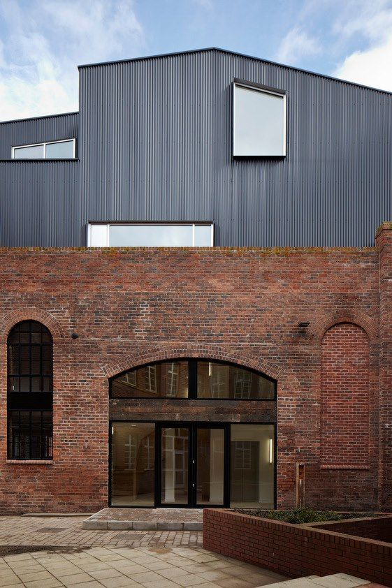 This rusted steel, windowed facade springs up between the historical limestone buildings of this old Flour Mill. More info and images at http://archdai.ly/XE3qFN  — Rotermann's Old and New Flour Storage / HGA