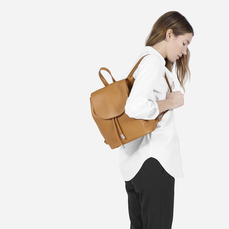 Ease meets elegance with this new luxury backpack. It features ultrasuede lining, feet to protect the bag's base, a hidden loop for secure closure, an interior snap pocket, and a top handle for easy carry by hand. There is gunmetal-finish hardware on the leather drawstrings and at the feet.