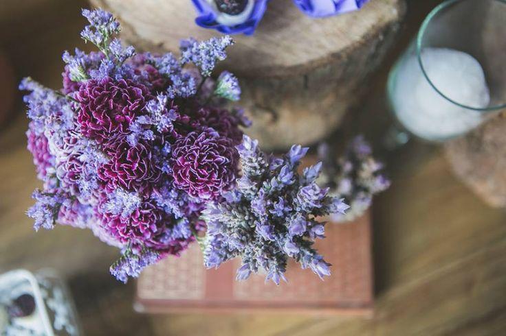 Decoração de casamento rústico chique com lavandas, livros antigos, velas e troncos. Essa flor roxinha se chama saudade, o que deixa tudo ainda mais cheio de significado.