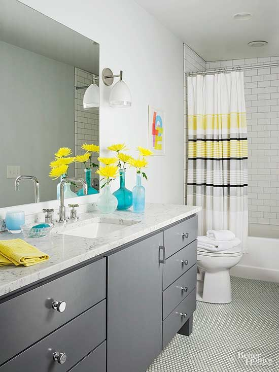 Soft graywallslend a neutral backdrop for sunny yellow and sky blue accents in this calmingbathroom. The stripedshower curtainfeatures a cheery striped motif, that picks up on the bathroom's accessories, linens, and gray painted vanity./