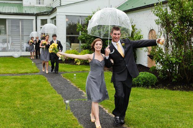 groomsman and bridesmaid walk with umbrella