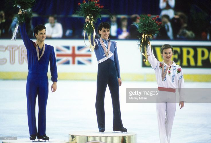 USA Brian Boitano (silver), Canada Brian Orser (gold), and Soviet Union Alexander Fadeev (bronze) with medals and flowers on medal stand after Men's Singles competition at Riverfront Coliseum. Manny Millan F26 )