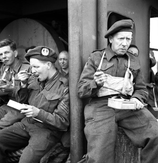 Canadian infantrymen from various units, including The Cameron Highlanders of Ottawa (M.G.), eating a meal aboard ship en route to the Normandy beachhead, 6 June 1944. Photographer: Ken Bell