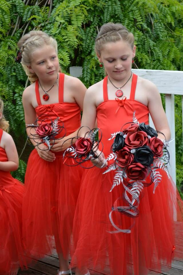 Flower girls with their single flower posy's to match this brides waterfall bouquet in red, black & silver. www.flaxation.co.nz