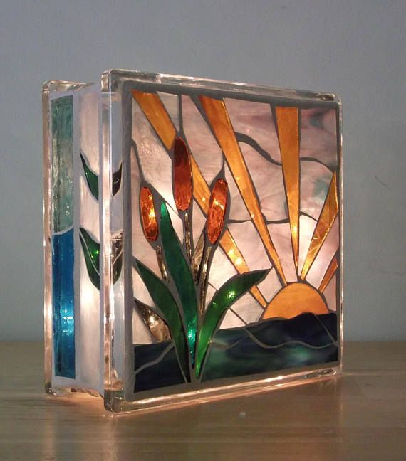 A brilliant stained glass light to enjoy in two different patterns. One side a water lily scene in shades of pink, dark green, light green textured, and a rich turquoise. On the other side a few cattails in green, golden yellow, pale blue and dark blue green. Made of stained glass,