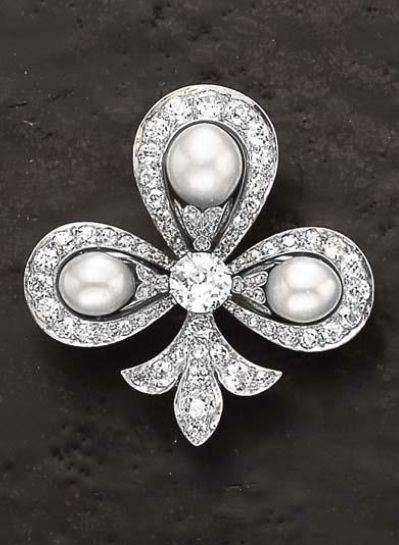 An Art Deco Diamond and Pearl Brooch  Designed as a circular-cut and rose-cut diamond fleur-de-lys,  set to the center with circular-cut diamond extending three pearls within an old-cut diamond surround, mounted in silver and gold.  The pearls have not been tested for natural origin.