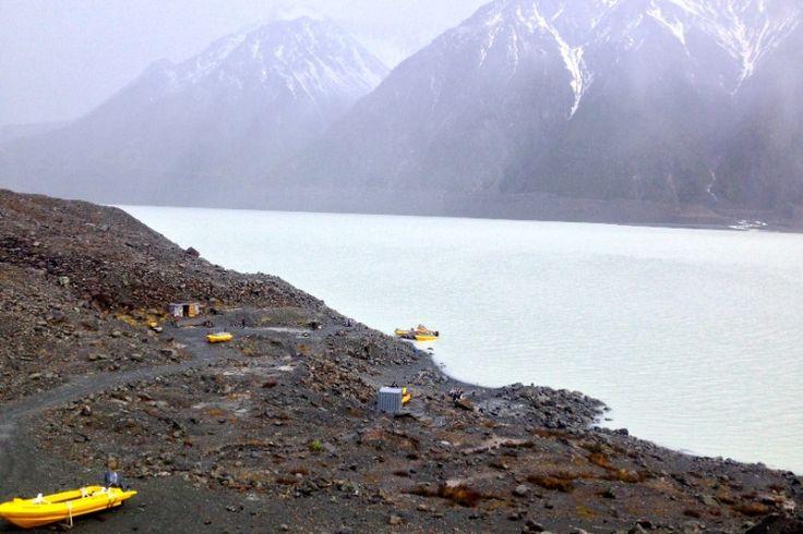 Botes aguardam turistas para o passeio no gelado lago Tasman, localizado no Mount Cook National Park. O aspecto leitoso da água é consequência do atrito do deslocamento do gelo e da rocha da montanha durante o período glacial, há milhares de anos