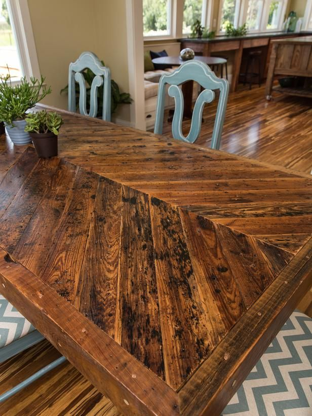Original roofing planks from the house were salvaged and arranged in a chevron pattern to create a custom dining room table.