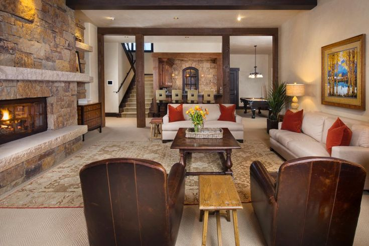 This rustic game room features two neutral leather sofas with red throw pillows, as well as two brown leather armchairs, allowing plenty of room for kicking back in front of the stone fireplace. The open floor plan allows for easy transition to the bar and pool table areas, making it the perfect space for entertaining.