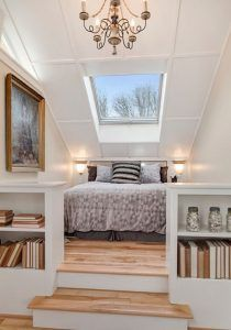 Two-tier attic master bedroom in Scandinavian design with light wood floors, built-in bookshelves and large skylight with white walls.