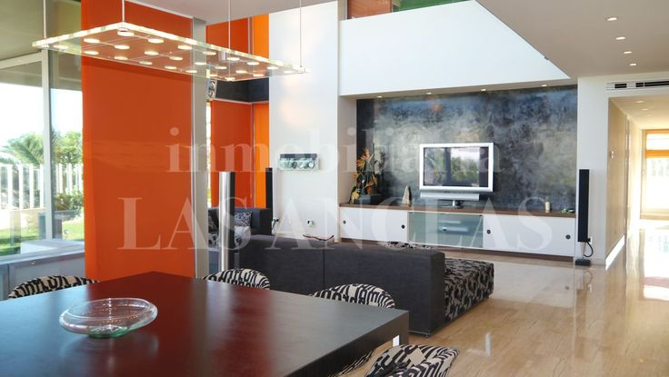 Very sleek, modern living-/dining room with double-heigh ceilings in property