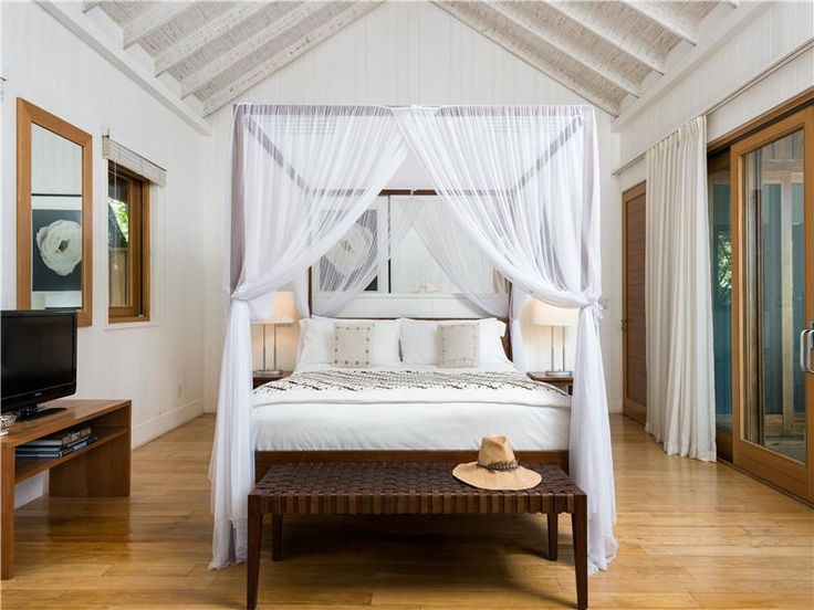 Christie Brinkley | A neutral color palette of whites and sandy beiges can be found throughout the supermodel's Caribbean beach house. Here, a sheer canopy adds romance to a four-poster bed. | #celebritiesathome #celebrityhousepictures #starshomes | See also: http://www.celebrityhomes.eu/