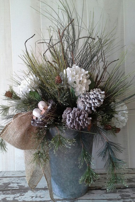 ★★★SALE - FOR 10% OFF USE COUPON CODE HOLIDAYS ( This item only )★★★ *****Large Rustic Winter Arrangement***** *****Shipping listed may be less depending on your ship zone.***** This beautiful life like arrangement is sure to bring some rustic charm to your home this Holiday season. I filled this galvanized bucket with lots of quality, life like pine greenery, white hydrangeas, pine cones and a sweet little birds nest with 2 glittered eggs. Finished with a burlap bow. Finished arr...