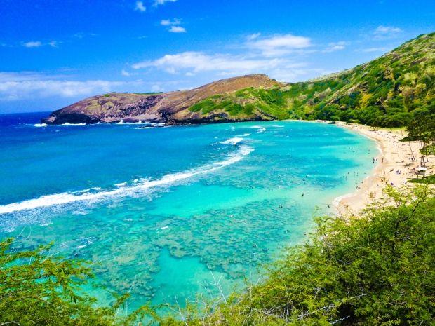"""Hawaii; de mooiste witte stranden, met een azuur blauwe zee, en het regenwoud op de achtergrond. Kauna'oa Bay ligt op het grootste eiland, met de toepasselijke naam """"Big Island""""."""