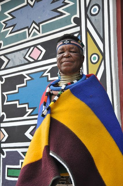 Africa |  Esther Mahlangu outside her beautiful traditionally Ndebele painted home in Nkangala, Mpumalanga, South Africa | © Lauren Barkume. BelAfrique your personal travel planner - www.BelAfrique.com