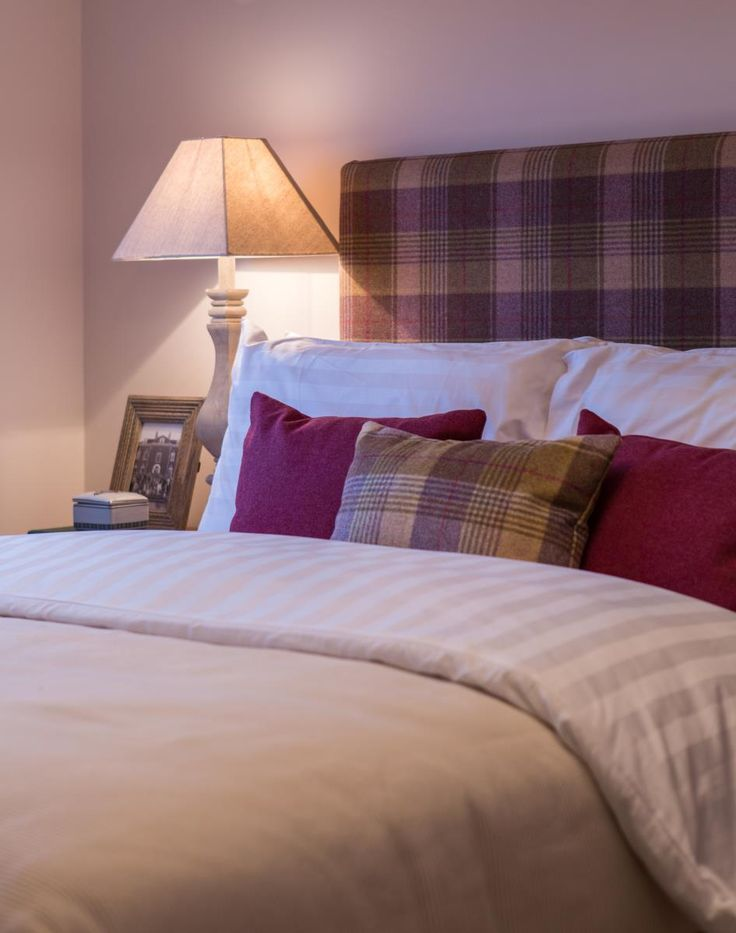 Check headboard with matching mulberry cushions all set against neutral bed linen #Inspiration