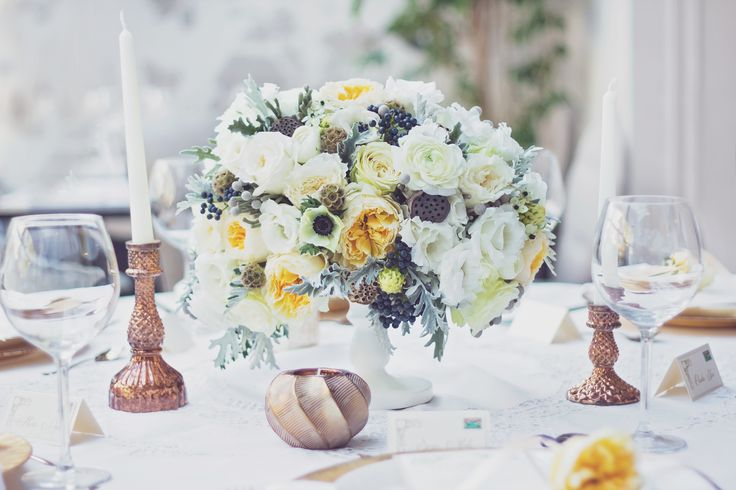 Sophisticated wedding inspiration. Bright autumn centerpiece of ranunculus, anemones, dusty miller and garden roses.