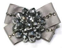Holiday Glitz Hair Bow. Bring on the bling and gear up for a special occasion with this gorgeous creation. From a very high end manufacturer – this bow is a STEAL and isn't just for girls. It looks great with everything from jeans to an evening dress.    Made with real glass beads, this bow is a true gem. Pewter colored beads and rhinestones on light grey ribbon. Mounted on a small french clip. Ages 12 and up. This bow contains small glass beads and is NOT recommended for infants.