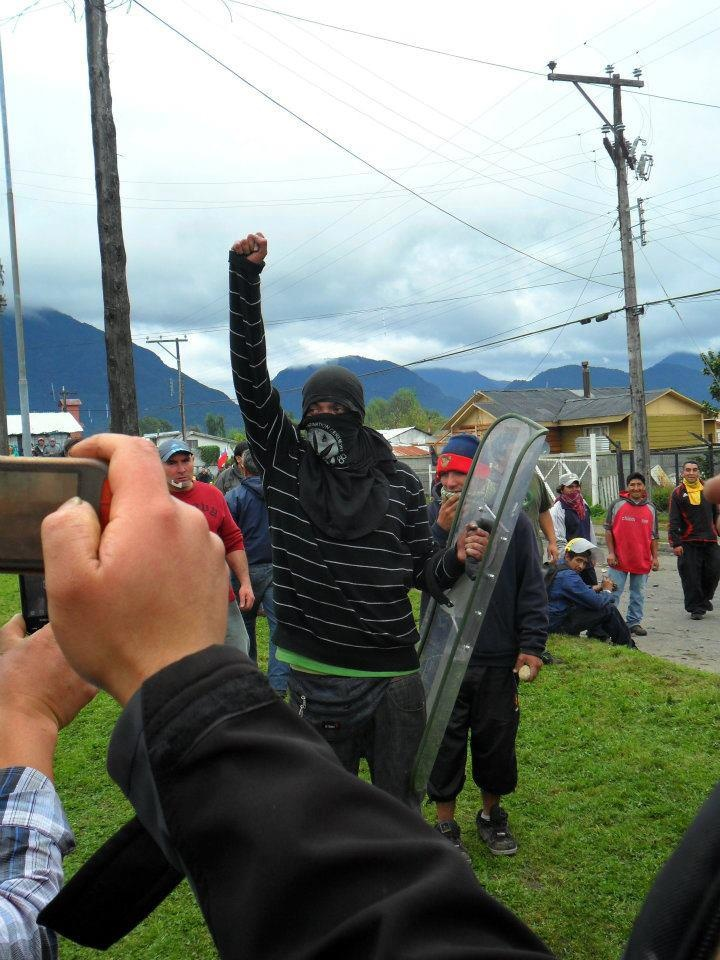 manifestante celebra trofeo, escudo de carabineros.