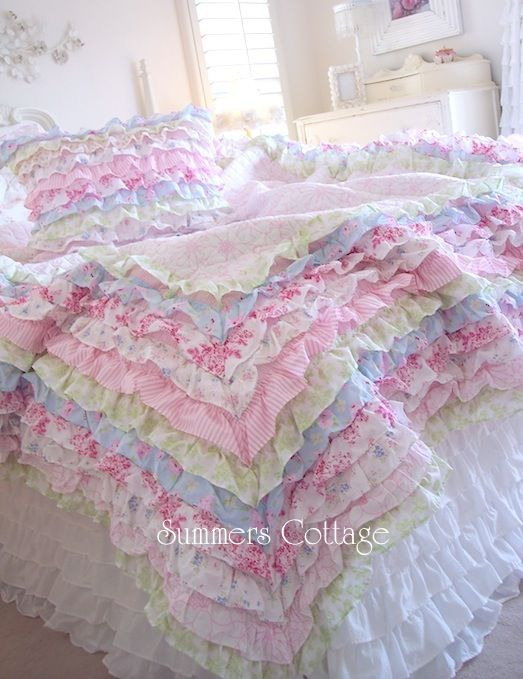 Overly cute ruffle quilt. @Tess Myers. I LOVE this. especially that one layer that is white with the pink flowers on it (3rd layer from the top) very unique and diff. see, if I come visit, we could go fabric shopping and make this together. :-?