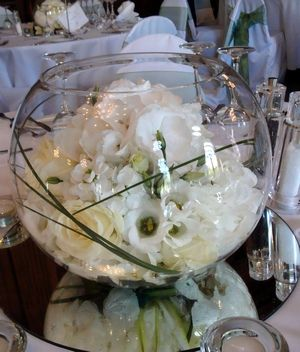 """Wedding Flowers """"White wedding flowers are perfect for classical, elegant weddings. This striking  display really sparkles -  glass fish bowl vase filled with large domes of ivory Avalanche roses, ivory lisianthus, scented stocks and hydrangeas.  """""""