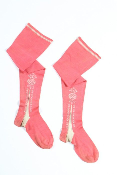 Pair of woman's stockings, England of France, 1750-1770. Frame-knitted salmon-pink silk with decorative clocks worked in ivory silk with sprigs, roses and crowns, stripped upper edge.