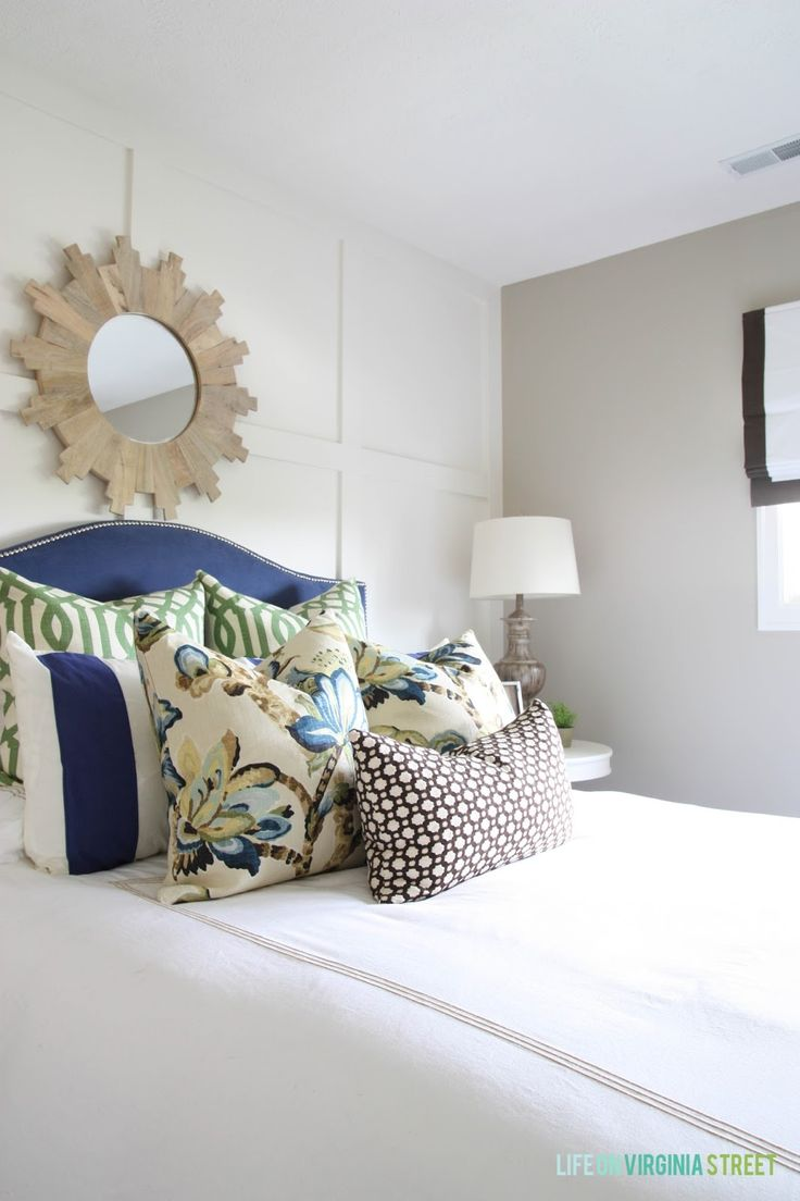 Guest bedroom with blue headboard, white board and batten walls, wood sunburst mirror and designer pillows