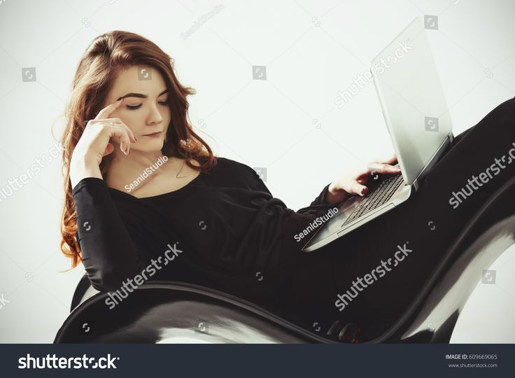 Thoughtful woman lying with a laptop