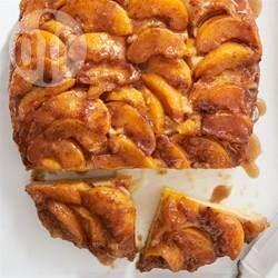 Perziken uit blik worden gekaramelliseerd met bruine suiker op de bodem van een slowcooker voor een warme cake, op de kop gebakken!