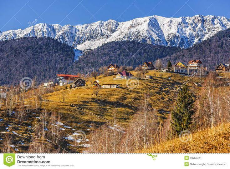 Sunny winter rural scenery with snowy Piatra Craiului mountain ridge and small village uphill in Pestera village, Brasov county, Romania.