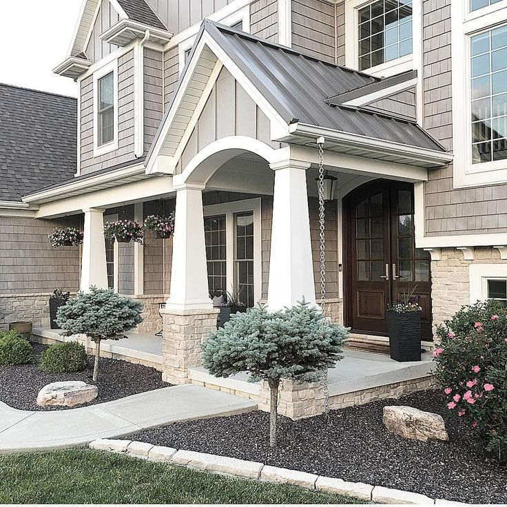 @carolineondesign Shaker style home with Mastic vinyl shake shingles. Grey home exterior. Stone and shake Shingle exterior. Metal roof. Shadow rock landscaping. Front porch with columns.