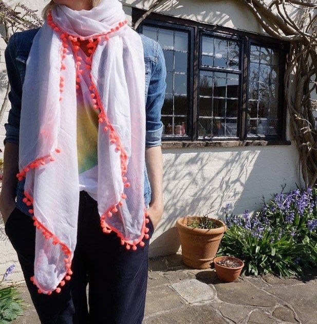 A neon pink pom pom scarf. The perfect Spring/Summer accessory.