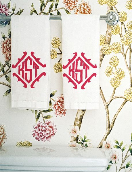 A bold, hot pink monogram pops against a floral wallpapered bathroom.