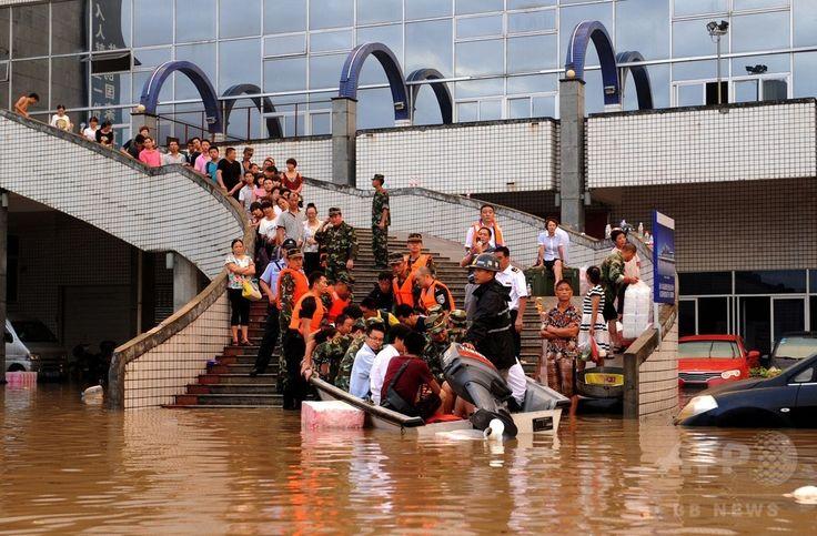 豪雨による洪水に見舞われた中国東部・浙江(Zhejiang)省麗水(Lishui)の駅に取り残され、ボートで救助される人たち(2014年8月20日撮影)。(c)AFP ▼23Aug2014AFP|中国・浙江省で豪雨、2万人以上が避難 http://www.afpbb.com/articles/-/3023898 #Flood