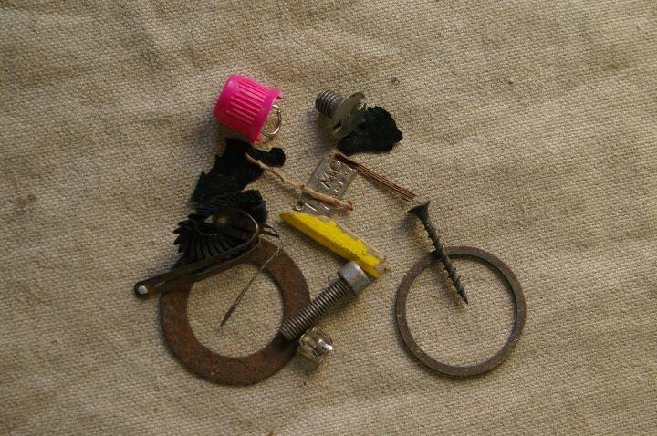 """Found in public places and recycled by straatjutter. """"Achterop / On a Pillion"""", 26.01.2012 Louis Armstronglaan Leidsche Rijn: Verbogen haarclip, 2x ijzeren ring, 3x schroef, 2x takje, 2x stuk plastic, roze dop, stuk potlood, knoophuls, ijzeren plaatje, schakel, verbogen ring"""
