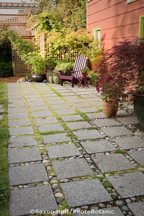 permeable patio with concrete aggregate pavers for water drainage in backyard garden