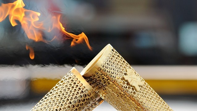 The kiss of the flame as it is passed from one to another on the 2012 Olympic Torch Relay.