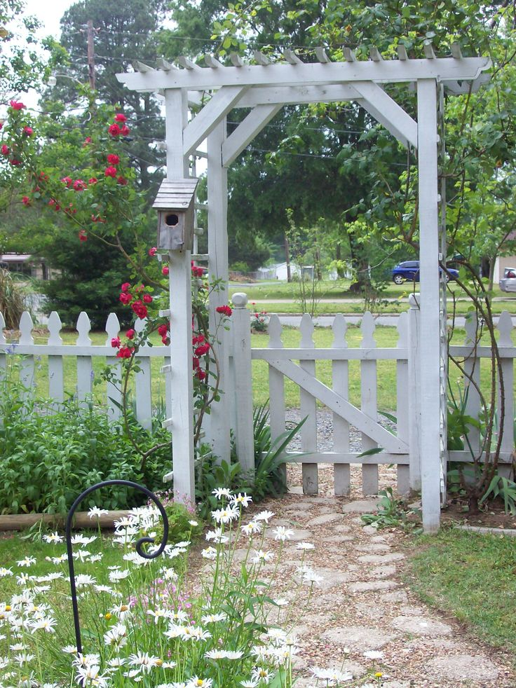 TX - White picket fences and rose arbors. I drew out the design for my cottage garden, researching plants that would do well in our area. The sidewalk is a mixture of concrete cobblestones and pea gravel.