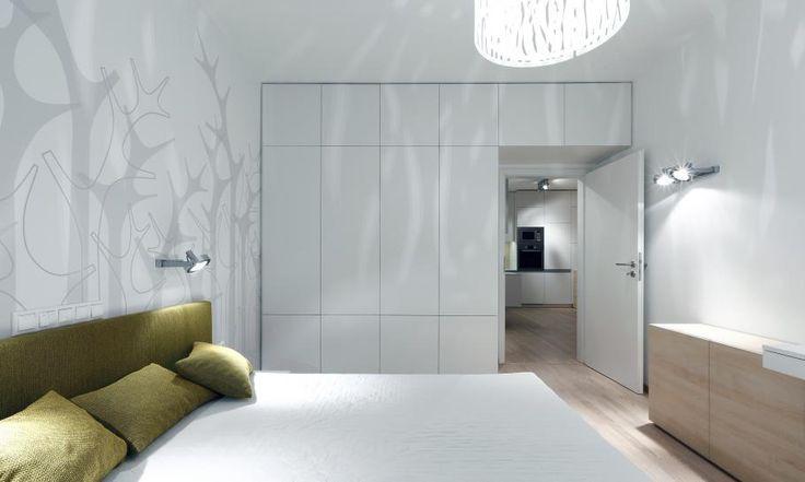 Úložné priestory v spálni navrhujeme tak, aby boli čo najďalej od okna, aby neznižovali pôdorys presvetlených častí izby. Bielu šatníkovú skriňu s dverami sme navrhli na celú stenu miestnosti a pokračuje aj nad dverami kvôli maximálnemu využitiu priestoru. Skriňa má matný laminátový povrch, ktorý sa dobre udržuje a je cenovo dostupný.