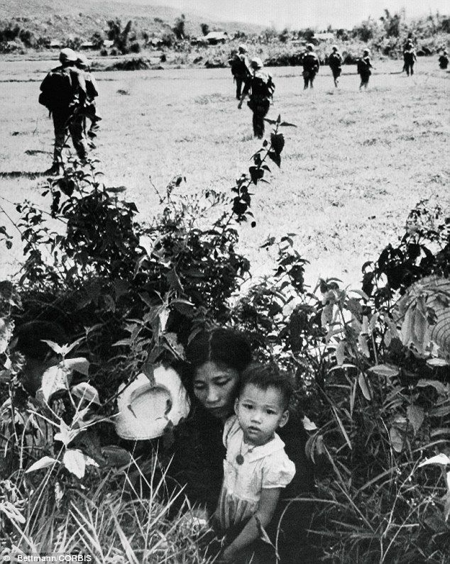 """In this 15 May 1965 photo, a Vietnamese mother and her [child] hide in bushes near Le My to escape fighting as U.S. Marines go past after clearing the village of Viet Cong forces.'"