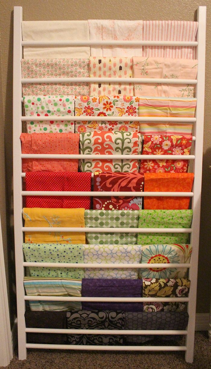 Repurpose the side of an older crib for fabric storage - It would be great for the fabrics I've already pressed and am waiting to cut! #repurposed #fabricstorage: