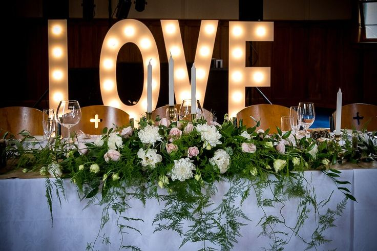 L.O.V.E in lights hire from Miss Frou Frou, Havelock North - provides a dramatic backdrop to the bridal table - Wedding of Jamie and Beth, January 2017 - a starry sky of fairylights over long tables overflowing with rose gold candlesticks and rustic wooden candle holders, olive branches and vases of soft pink flowers created a romantic vintage look in the Chapel, Mission Estate Winery, HAWKES Bay.