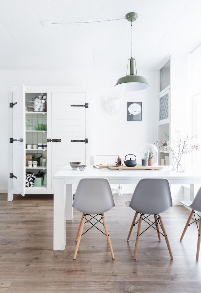 White Kitchen With White Table, Brown Wooden Floors, Grey Chairs And White  Storage Units