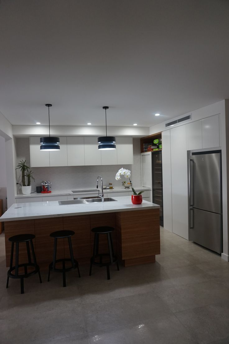 Two tone kitchen using polyurethane and timber veneer 40mm stone bench top glass splash back Pendant lighting over island Step in pantry Wine fridge