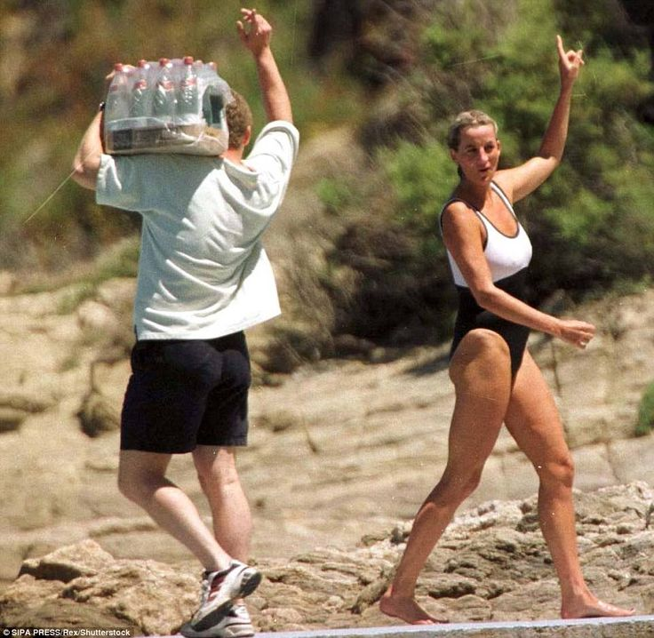 On holiday in St Tropez in July 1997, Diana's a vision in symmetry as a delivery boy in matching black and white passes her on the beach