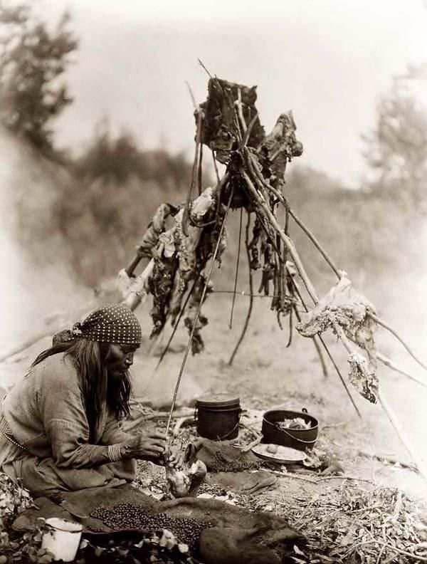 You are looking at an intriguing picture of Sarsi Kitchen. It was taken in 1927 by Edward S. Curtis.    The picture presents a Sarsi Indian woman cooking over campfire, in Alberta, Canada.    We have created this collection of pictures primarily to serve as an easy to access educational tool. Contact curator@old-picture.com.    Image ID# 63DB7347