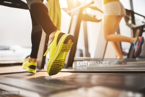 Stock Photo : Unrecognizable people running on treadmills in a gym.